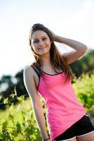 gesunde fröhliche junge Frau des Fitnesssports, die Landschaft im Freien läuft foto