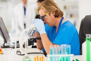 medizinischer Forscher, der mit Mikroskop arbeitet