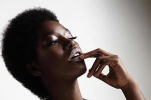 Schönheit schwarze Frau, die Abend Make-up und Afro-Haare trägt foto
