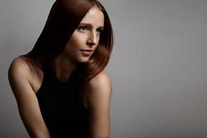 rothaariges Mädchen mit blauen Augen auf grauem Hintergrund