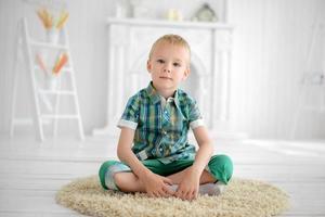 kleines nachdenkliches Jungenkind, das zu Hause auf dem Boden sitzt