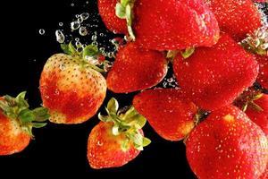 Erdbeeren fallen in Wasser bei schwarzem Hintergrund foto