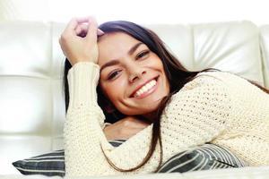 fröhliche schöne Frau, die auf dem Sofa liegt foto