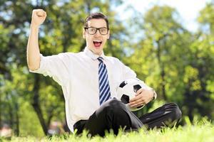 junger fröhlicher Mann, der einen Ball hält und Glück gestikuliert foto