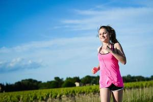 Fitness Sport gesunde und fröhliche junge Frau im Freien laufen foto