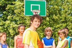 lächelnder Junge mit Freunden hinter während des Basketballs foto