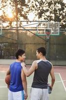 Freunde, die nach einem Eins-zu-Eins-Basketballspiel nach Hause gehen foto