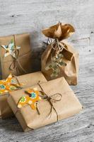 Weihnachtsgeschenke in Kraftpapier auf der hellen Holzoberfläche