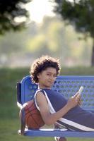 Afroamerikanerjunge, der eine mobile Tablette im Park liest foto