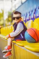 stilvoller kleiner Junge, der am Basketballplatz aufwirft foto