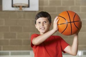 Junge, der während des Basketballspiels in der Turnhalle schießt foto