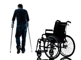 verletzter Mann mit Krücken, die weg von der Rollstuhlsilhouette gehen foto