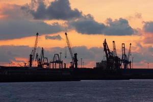 Kräne im Hafen von Bilbao bei Sonnenuntergang