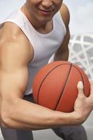 junger Mann, der Bizeps zeigt und Basketball hält foto