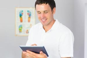 hübscher fröhlicher Physiotherapeut mit Tablette foto