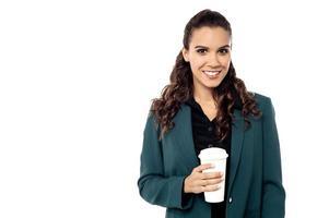 fröhliche Geschäftsfrau, die eine Tasse hält foto