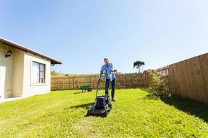 fröhlicher junger Mann, der Rasen mäht foto