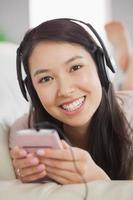 fröhliches asiatisches Mädchen, das Musik hört