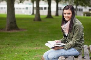 fröhlicher brünetter Student, der auf Banklesung sitzt foto