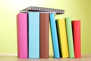 Bücher mit Briefpapier auf Holztisch auf grünem Hintergrund foto