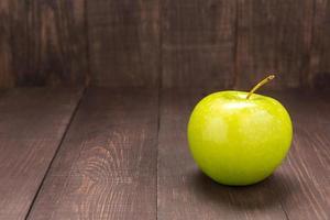 grüner Apfel im hölzernen Hintergrund. Speicherplatz kopieren foto