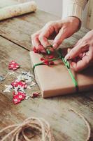 Frau, die moderne Weihnachtsgeschenke verpackt, präsentiert zu Hause