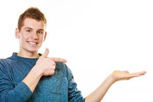 junger Mann, der offene Handfläche hält, die Kopienraum zeigt foto