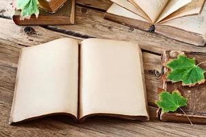 offenes leeres Buch auf Holzschreibtisch mit Herbstahornblättern foto