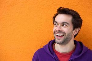 lächelndes Gesicht des jungen Mannes, der Kopierraum betrachtet foto