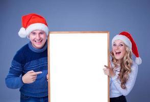 Weihnachtspaar hält weiße Tafel mit leerem Kopienraum foto