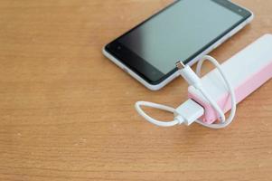 Smartphone mit Powerbank auf Holzschreibtisch und Kopierraum foto