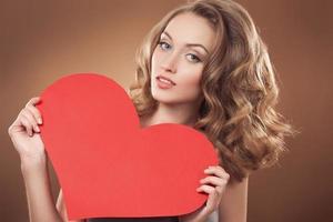 Frau, die Valentinstag-Herzzeichen mit Kopienraum hält foto