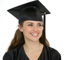 Porträt des lächelnden Abschlussmädchens, das auf Kopienraum schaut foto