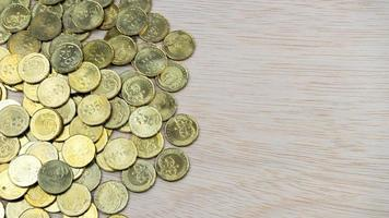 Draufsichtmünzen auf hölzerner Schreibtischoberfläche mit Kopierraum foto