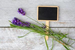 weißer hölzerner Hintergrund mit Lavendel, Tafel und leerem Kopienraum foto
