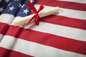 Band umwickeltes Diplom, das auf amerikanischer Flagge mit Kopienraum ruht foto