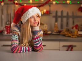 Teenager-Mädchen, das auf Kopienraum in der weihnachtlich dekorierten Küche schaut foto