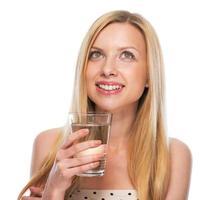 Teenager-Mädchen mit Tasse Wasser, das auf Kopienraum schaut foto