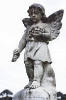 verwitterte Statue des kleinen Engels gegen weißen Hintergrund, Kopienraum