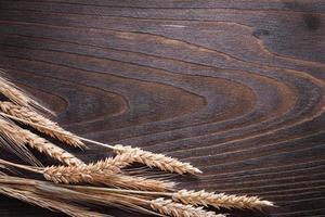 Kopieren Sie Raumbild von Weizenroggenohren auf hölzernem Weinlese foto