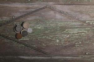 Draufsichtmünzen auf altem hölzernem Schreibtisch mit Kopienraum foto
