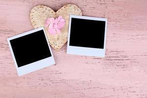 leere alte Fotos und dekoratives Herz auf farbigem hölzernem Hintergrund