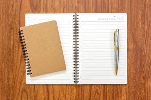 leeres Notizbuch mit einem Stift auf Holzhintergrund foto