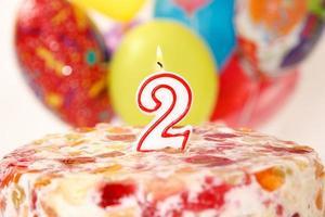 Geburtstagskerze mit Flamme und Luftballons foto