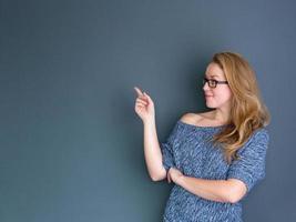 junge Frau zeigt Kopierraum foto