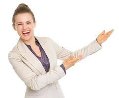 lächelnde Geschäftsfrau, die auf Kopienraum zeigt