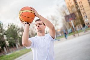 junger Mann, der sich darauf vorbereitet, einen Basketball zu schießen foto