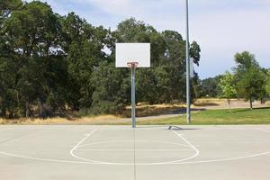 Basketballkorb mit weißem Rückenbrett und Platz foto