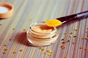 Schönheit und Make-up: Grundierungsprodukt mit Pinsel foto