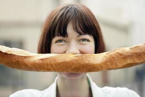 Frau hält Baguette vor Gesicht foto